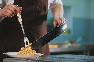 Chef serves spaghetti carbonara on the plate in restaurante