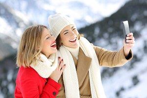 Two happy friends taking selfies