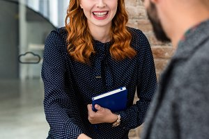 Smiling redhead woman greeting the recruiter at job interview