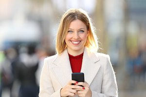woman wearing coat posing with phone