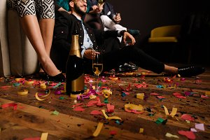 Bottle and glass of champagne on the confetti floor after party with people in background