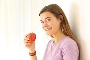 happy teen holding an apple