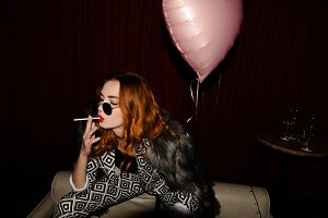 Posh redhead woman smoking a cigarrette at a party night