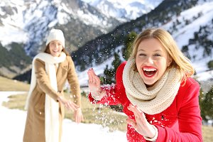 Two friends joking throwing snowball