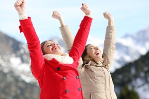 Two excited women raising arms