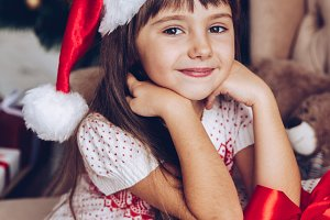 Girl in Santa  hat at home with gift