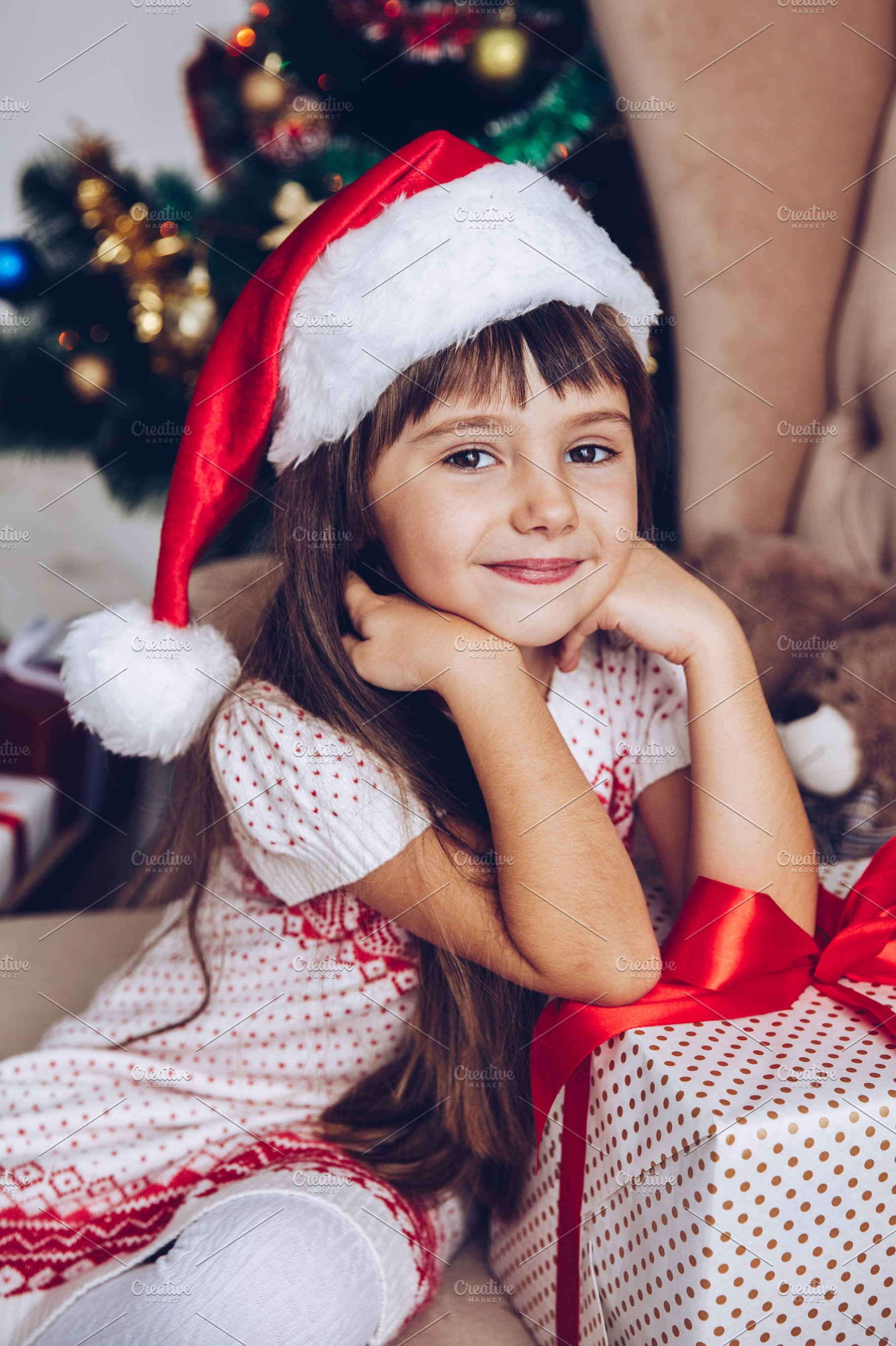 66d76eb75328c Girl in Santa hat at home with gift ~ People Photos ~ Creative Market