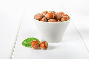 Walnut hazelnut in a white bowl on a white wooden table.