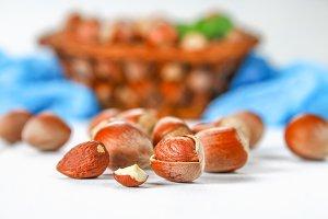 Walnut hazelnuts in a wicker basket on a white wooden table.