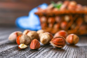 Walnut hazelnuts in a wicker basket on a brown wooden table.