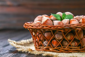 Walnut hazelnuts in a wicker basket on a brown wooden table.
