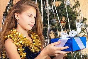 Beautiful teen girl near christmas tree happily looks at gift