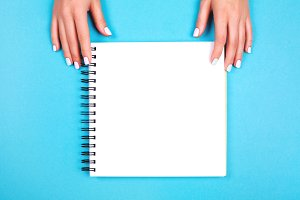 Two hands holding spiral notepad