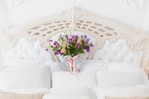 Among the pillows is a bouquet of th