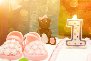 The cake baby girl pink one year booties, toys and a candle with the number 1