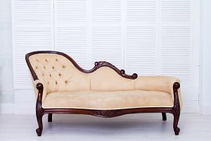 Luxury Interior . Carved Furniture. Beige textile classical style sofa in vintage room. White background