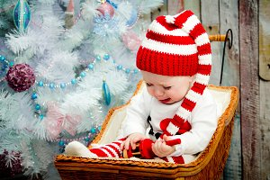 Crying and sad baby girl sitting under a blue tree in a striped hat red and white color. The concept of a new year. On a Christmas card