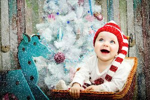 Smiling baby girl sitting under a blue tree in a striped hat red and white color. The concept of a new year. On a Christmas card