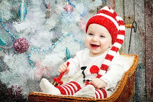 Smiling happy child sitting under a blue tree in a striped hat red and white color. The concept of a new year. On a Christmas card.