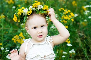 Portrait of a little girl in a wreath from wild flowers. Child closeup.