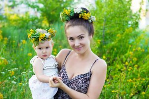 Portrait of mother and daughter wearing garlands of wild flowers.