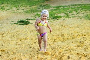 Child little funny and happy girl runs along the beach on the sand in a swimsuit