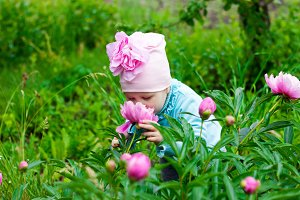 The little girl in the garden with peonies flowers.
