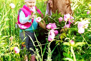 Baby girl with mother in the garden among the flowers.