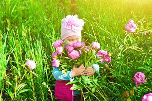Little girl in garden with a flower bouquet of peonies
