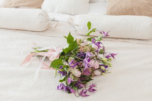 On the bed is a bouquet of flowers.