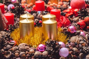 Wax candle of gold color with Christmas toys.