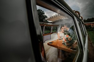 Wedding couple poses in an old bus
