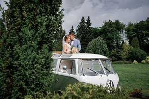 Bride and groom stand in a retro bus