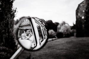 Wedding couple in car's back mirror