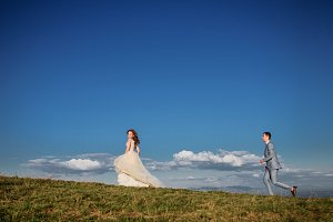 Bride runs from groom on the hill