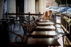 Couple sit in an empty street cafe
