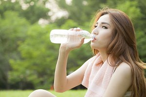 Woman sit and drink after exercise.