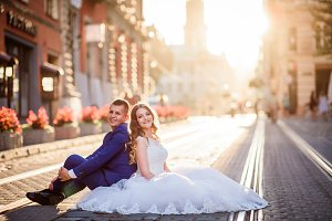 Newlyweds sit on an old street