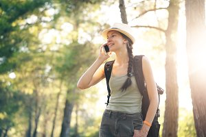 Young tourist girl backpacker in hat chatting with smartphone during walking in summer forest