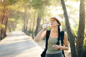 Attractive young tourist girl refreshing by drinking water after backpacker journey