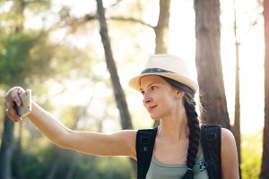 Young tourist girl backpacker in hat online video chatting with smartphone during walking in summer forest
