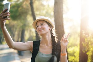 Funny tourist girl in hat taking selfie photos with smartphone camera during travelling and hitchhiking