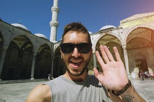 Handheld of Happy tourist man having online video chat using his smartphone camera near famous blue mosque in Istanbul