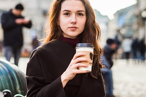 The girl holds coffee in her hand