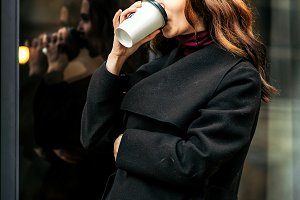 Brunette girl drinks coffee