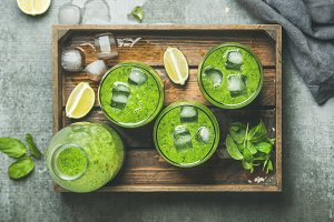 Fresh green smoothie with ice cubes, mint, lime in tray