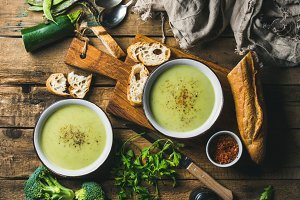 Two bowls of homemade pea, broccoli and zucchini cream soup