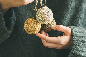Woman in grey sweater holding decorative golden balls in hands