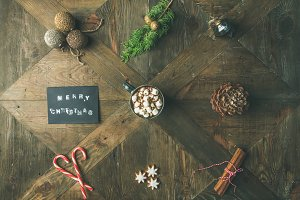 Flat-lay of greeting card, hot chocolate, candy cane, pine cone