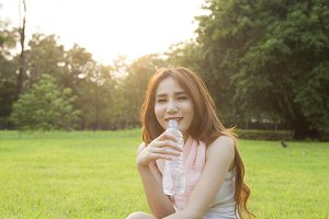 Woman drinking water and sit on gras